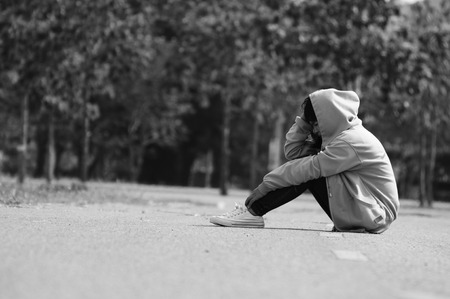 doleful: Nervous and Lonely Girl Sitting on the Road Stock Photo