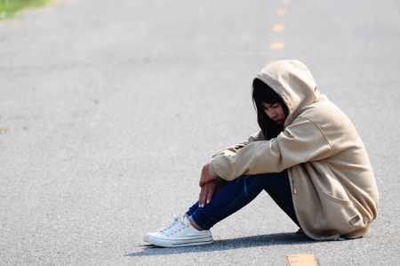 dejected: Nervous Girl Sitting on the Road