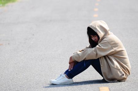 doleful: Nervous Girl Sitting on the Road