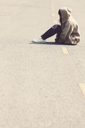 heartbroken: Sad and Heartbroken Girl Sitting on the Road Vintage Stock Photo