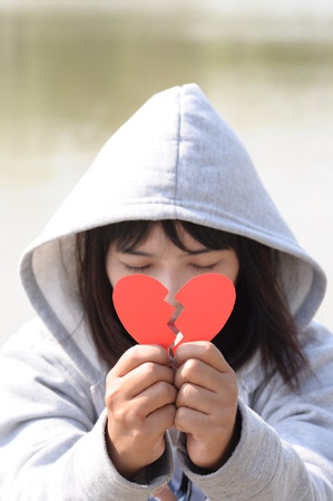 to confess love: Sad Girl Praying to Reconcile with Red Broken Heart Shape