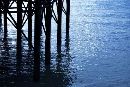 Reflections in the water under a pier.