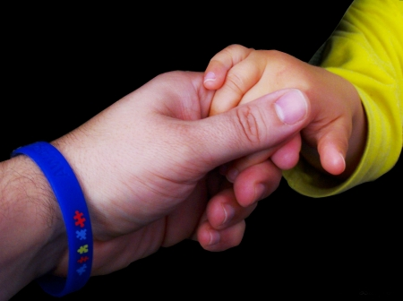adult hand with an autism awareness wrist band holding a baby hand Stock Photo