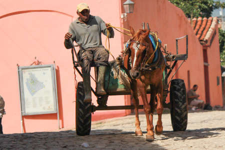 Trinidad, Cuba 14.12.2018 Horse and cart transport for goods and pink building Imagens