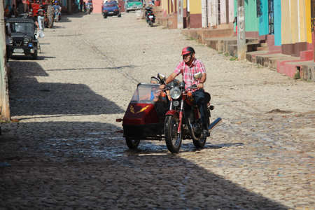 Trinidad, Cuba, 16.12.2018 Motorcycle with sidecar and passenger in the street