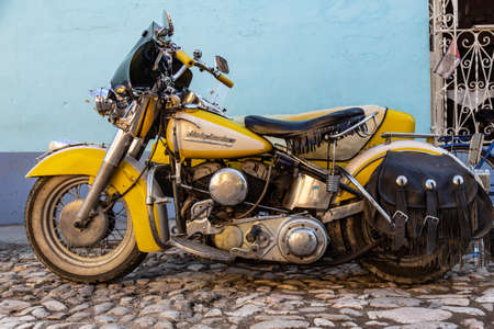 Trinidad, Cuba, 16.12.2018 Yellow motorcycle in the street with tasseled seat