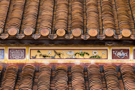 Hue, ancient capital of Vietnam. Yellow enamelled roof tiles architecture detail