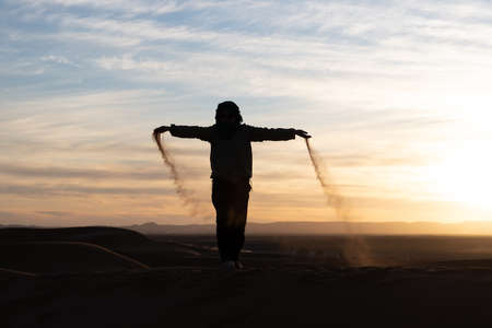 Silhouette of person jumping and throwing sand in the Sahara against a sunset