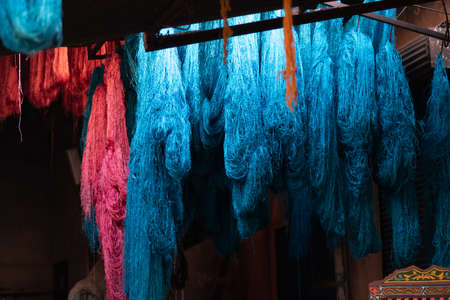 Dyed wool hanging to dry in souk in Marrakech Morocco, red, blue, yellow, gold