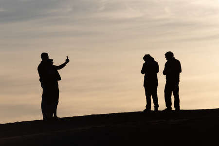 Silhouettes of tourists taking pictures at sunset in the Sahara desert Morocco Banco de Imagens