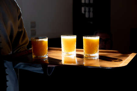 Orange juice in glasses being served on tray backlit by sun in Marrakech Morocco