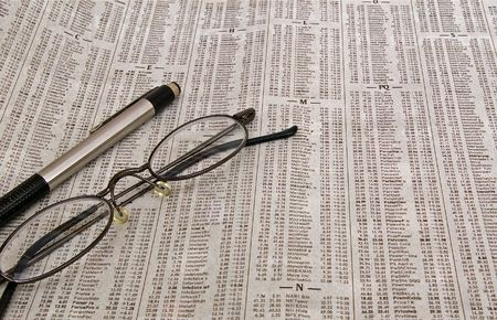 Image of a pair of glasses and a pen sitting on the stock market report