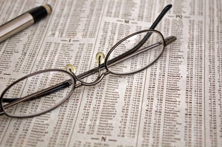 bifocals: Image of a pair of glasses and a pen sitting on the stock market report
