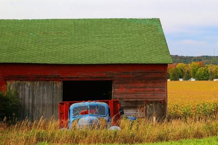 run down: Run down blue truck parked in front of an old red barn in the country