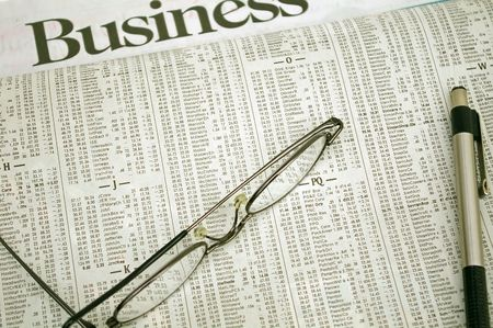 Pair of glasses and a pen resting on a newspaper's business section Imagens