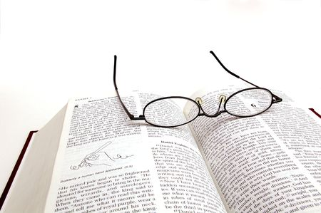 codex: Pair of glasses resting on an open bible Stock Photo