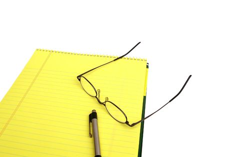 legal pad: Pen and glasses resting on a yellow legal pad