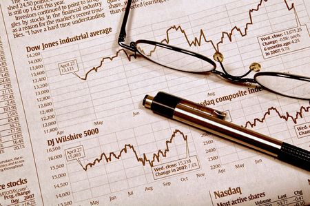 Pen and glasses resting on a stock market chart photo