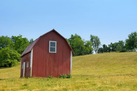 Small red barn on a hillside in the country