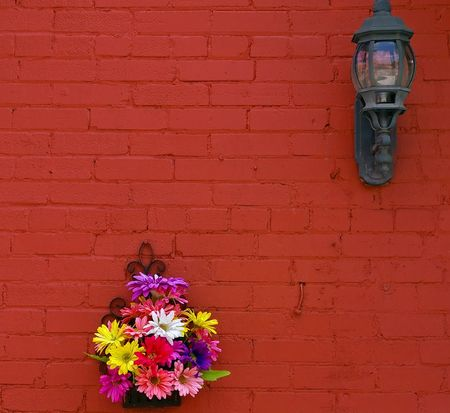 Red brick wall with a street light and a basket of flowers