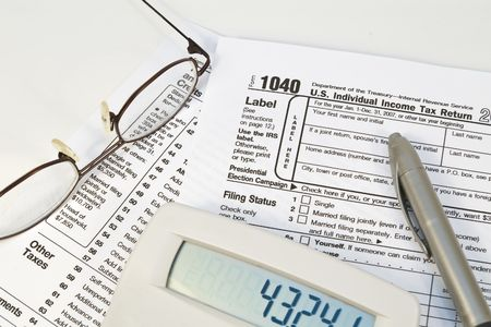 IRS 1040 form with glasses, pen, and calculator Stock Photo