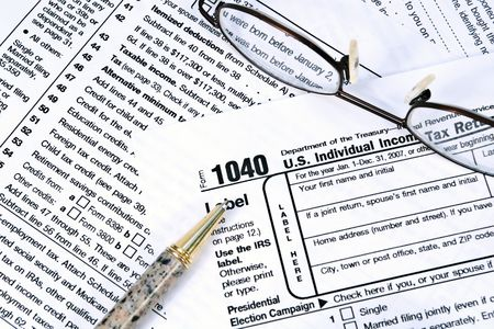 IRS 1040 income tax forms with a pair of glasses and a pen.