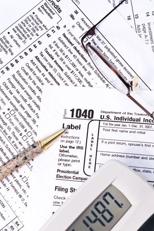 IRS 1040 income tax forms with glasses, pen, and a calculator. Imagens