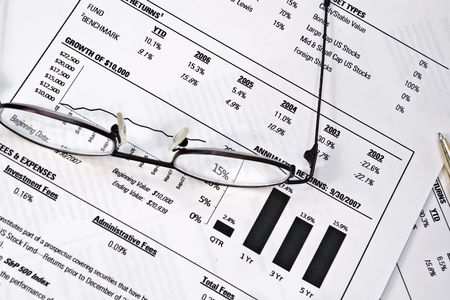 Monthly investment fund report with pair of glasses