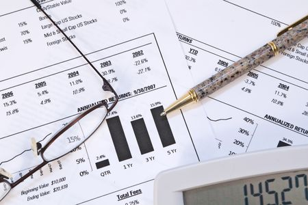 bifocals: Monthly stock investment report with pair of glasses, pen, and calculator Stock Photo