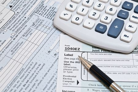 IRS 1040EZ income tax forms with pen and glasses
