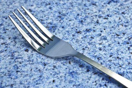 Silver fork on blue granite countertop Imagens