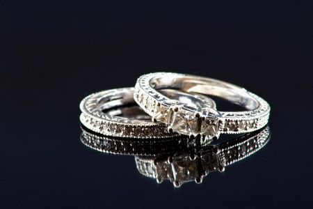 Diamond and white gold engagement ring and wedding band on a black reflective background