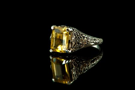 Fancy silver and citrine ring on black reflective background Imagens