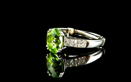Fancy silver and peridot ring on black reflective background