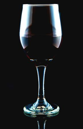 Crystal red wine glass on a black reflective background