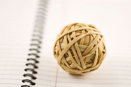 Rubber band ball on a notebook with shallow depth of field
