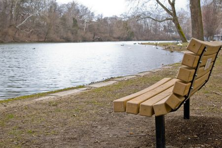 Empty park bench facing a small lake Imagens