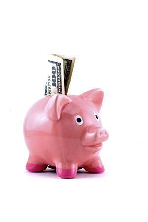 Pink piggy bank with $100.00 bill in the slot Imagens