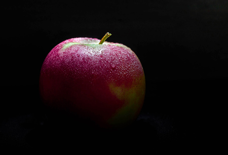 delicious red apple on black background
