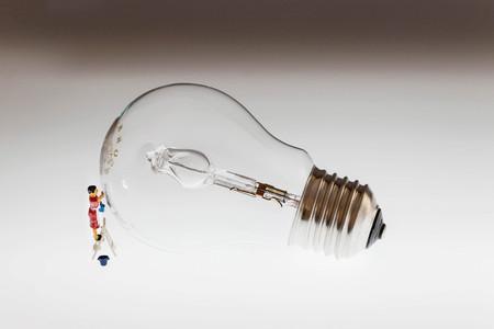 miniature woman cleaning a light bulb Фото со стока