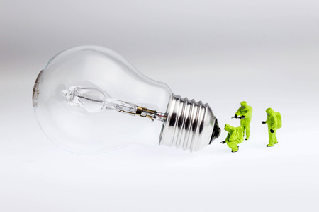 men in protective suits checking a light bulb