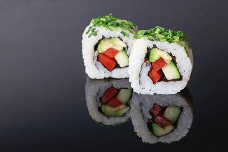 Sushi reflection on black acrylic plate