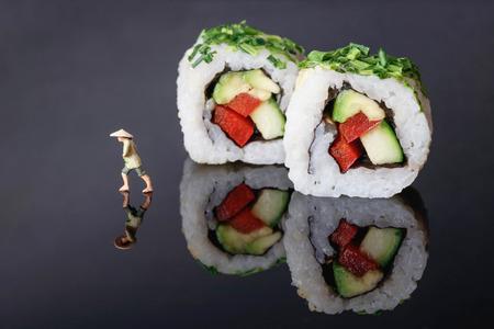 rice farmer made sushi roll on black acrylic plate