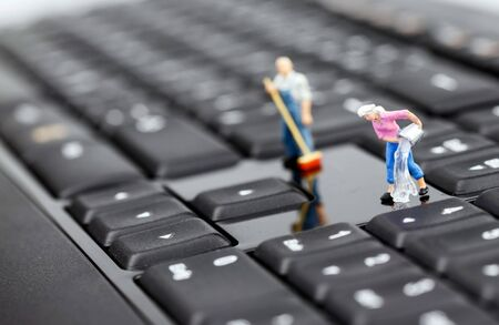 Miniature man and woman cleaning keyboard