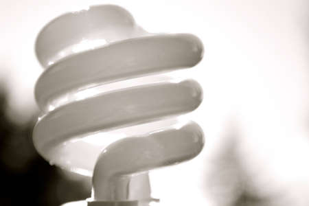 close-up of a compact fluorescent lightbulb on a blurry black and white background