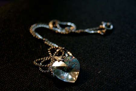 cutglass: Cut-glass heart-shaped necklace with chain on black textured background.