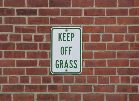 urging: Sign urging people to either stay off the lawn or not to smoke marijuana Stock Photo