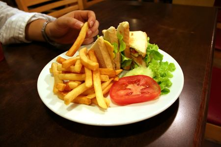 hoagie: Club sandwich, with french fries; hand reaching fora fry