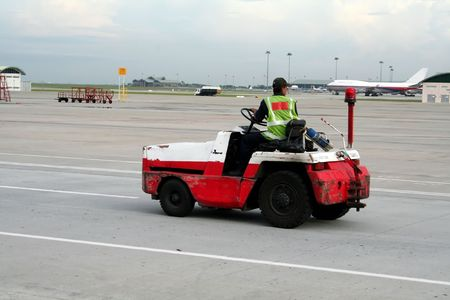 Airport worker on a vehicle, racing down the runway photo