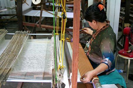 Woman weaving silk cloth in Thailand photo